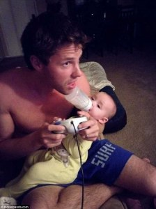 dad feeding baby playing videogames